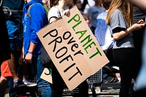 "A sign saying ""Planet Over Profit"""