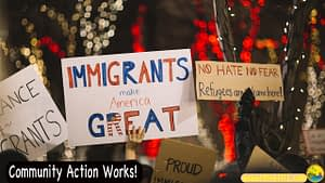 """A protest march, someone with a sign saying """"Immigrants Make America Great."""" At bottom left of photo are the words, """"Community Action Works!"""""""