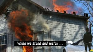 """A man stands and watches as his home burns. Words say, """"While we stand and watch ..."""""""