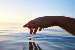 A hand poised over water, fingers making peaceful little ripples