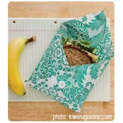 Colorful folded waxed cloth envelope showing sandwich inside, with a banana off to the left.