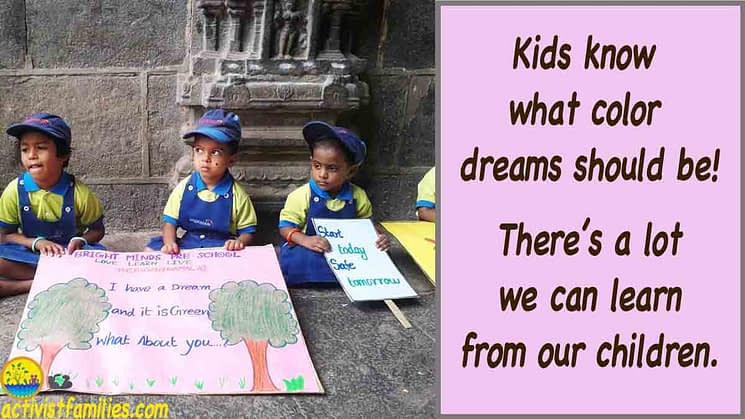 "Three pre-school boys sit on the floor listening to someone, holding signs they've painted for an eco-event. One large sign shows drawings of trees and flowers and the words, ""I have a dream, and it is green. What about you?"" Another sign says, ""Start today, safe tomorrow."" Large text to the right of the picture says, ""Kids know what color dreams should be!"""