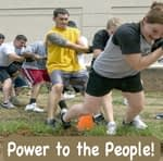 "Adult multiethnic tug of war, with the words ""Power to the People"" underneath"